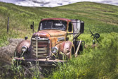 An old International truck sits abandoned in the rural hills of Washington State.
