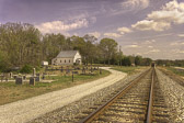 The image of this sweet little church in the rural Georgia countryside is moving.  The winding dirt road that skirts the cemetery leads your eye to the sanctuary nestled in the trees.  The road and the random placement of  headstones in the foreground is balanced with the ramrod straight rails supported by the cross ties and gravel bed.  And to top it off, there is a train coming.  It doesn't get any better than this for a Historic Rural Georgia Church and days gone by.