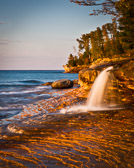 A beautiful (but tiny) waterfall on Lake Superior in the Upper Peninsula of Michigan. Believe it or not, this waterfall is only about two feet tall. But it spills out onto a beautiful bed of eroded sandstone. It's at a place called Miners Bridge and it is lovely at sunset (or at least in late afternoon light).