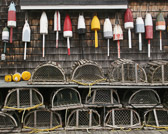 Classic Maine coastal imagery...lobster baskets and colorful bouys arorn the side of a weathered old shack.